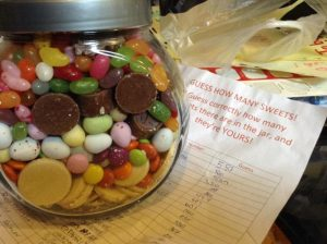 A jar of pick and mix sweets on top of a list of guesses