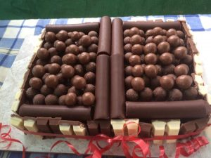 A rectangular chocolate cake edged in kitkats with a border of chocolate fingers and a ballpool of maltesers on top
