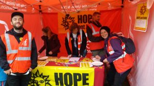 Festival stall with people in red high vis jackets sheltering from the rain and Hope Not Hate yellow banners displayed.