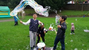 3 Roma children blow giant bubbles on the grass.