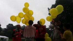 Children realise a dozen yellow balloons into a grey sky.