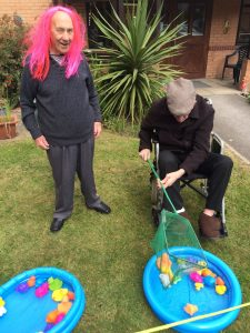 An old man in a wheelchair fishing for plastic ducks in a paddling pool with another an stood watching wearing a pink wig.