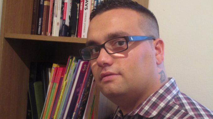 Headshot of a young Roma man in glasses by his bookshelf.
