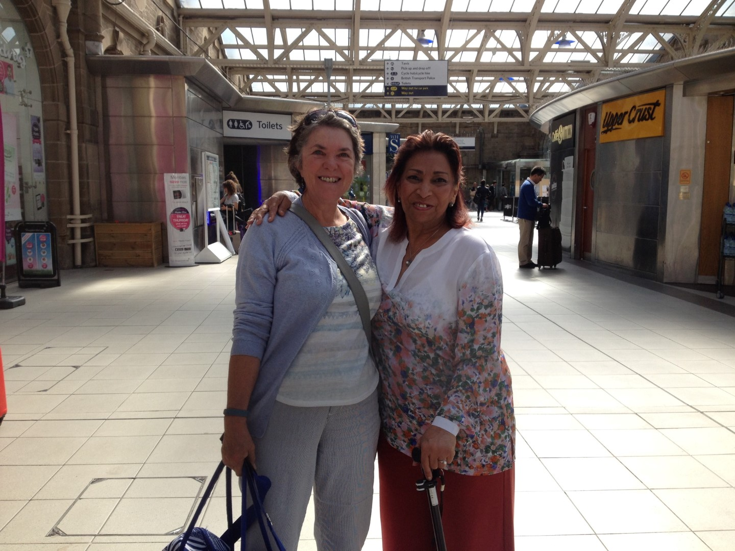 Two women in their 60s reunited at a train station.