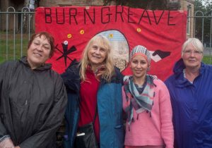 4 rained on women in from of a red banner saying 'Burngreave'