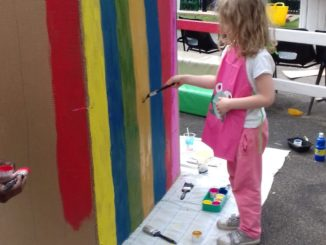 A little girl in pink overalls paints stripes on a cardboard beach hut