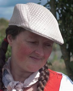 A woman with rosie cheeks and pigtails outdoors in a flat cap.