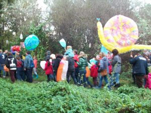 A crowd of people walk away with their lanterns, a large colourful snail in the foreground