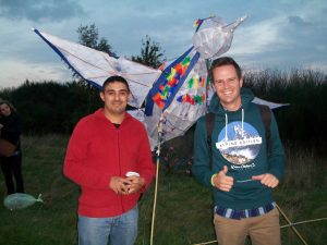 Two men smiling in front of a bird lantern made of tissue paper and willow, as dusks falls over the park