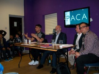 Panel of four men sat at a table in front of a screen saying PACA. One man is talking to audience