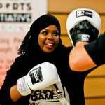 Muslim girl dressed in black, wearing white boxing gloves, sparing with a partner off the photo.