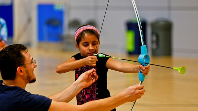 Girl, wearing a pink headband, taking aim with a bow and arrow with a man helping her by holding the bow string.