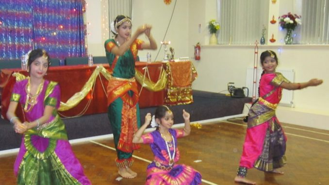 4 children in colourful sarees perform a traditional dance