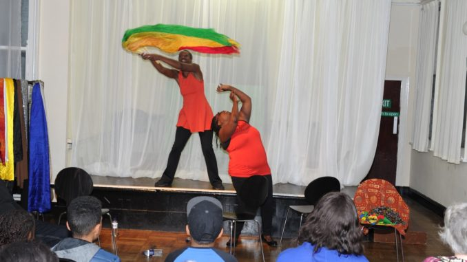 Two women performing on stage, one behind waving a red, yellow and green fabric in the air, the one in front looking up and gesturing upwards with her hand