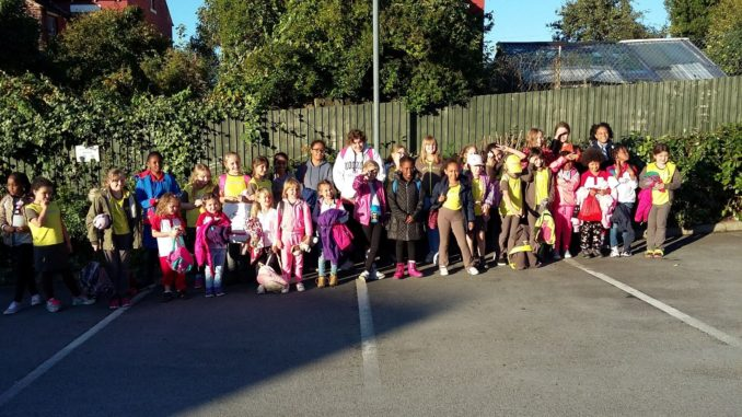 30 guides, brownies and rainbows posing in a car park waiting for their coach to the zoo.