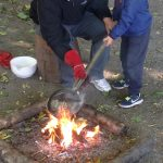 A man helps a small boy hold a pan over an outdoor fire.