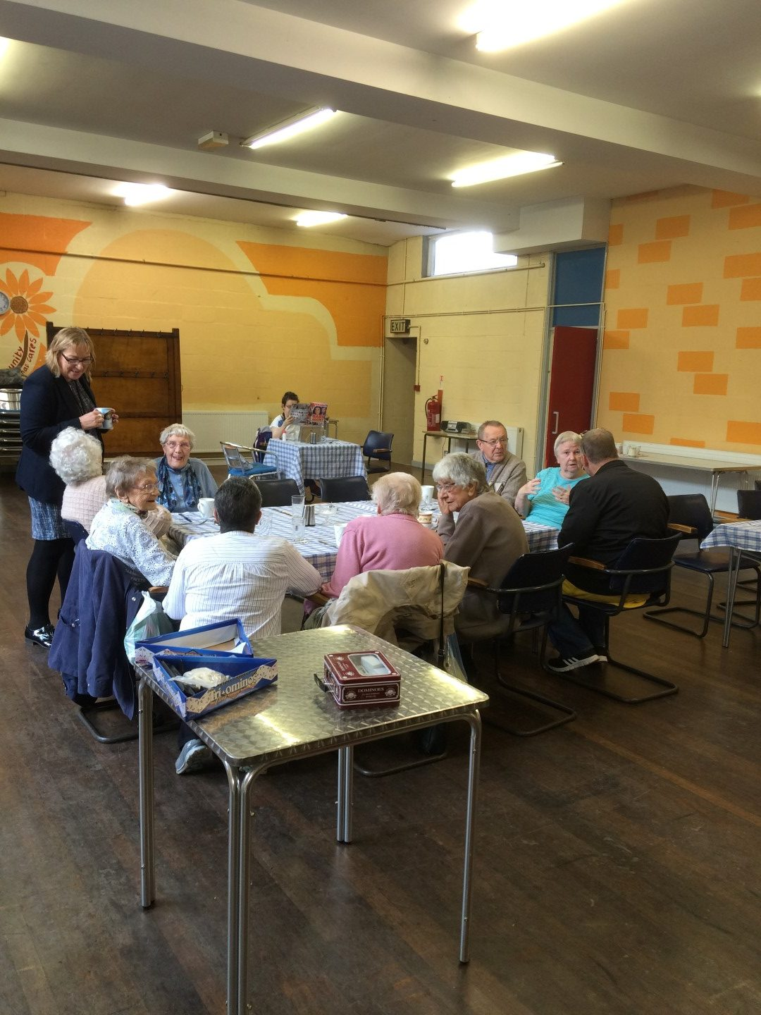 A group of older people having lunch in a church hall