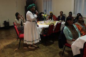 Afro-Caribbean woman in white dress and green headscarf stands and speaks into a microphone, to a group of women sat at tables