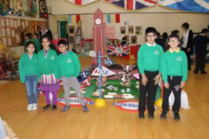5 key stage 2 children stood in front of a display of cardboard Big Ben, a tea party and a flag with the queen's face on it.