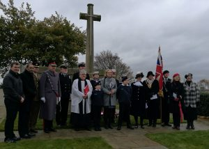 Councillors and vicar and cadets with a Union Flag gathered around the war memorial
