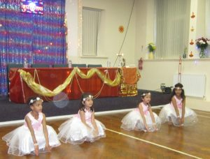 4 little girl ballerinas crouch down during their dance