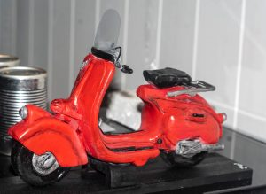 A red polymer clay motorcycle scooter.