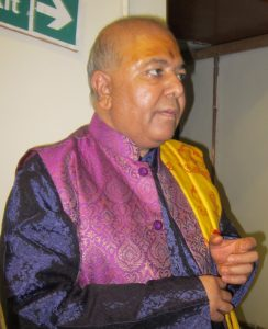 An Asian man in colourful Hindu ceremonial robes