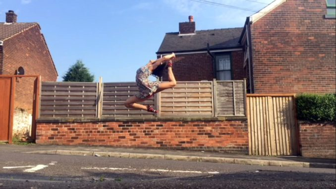 Ruby May doing an acrobatic leap, holding her foot behind her head in a Pitsmoor street