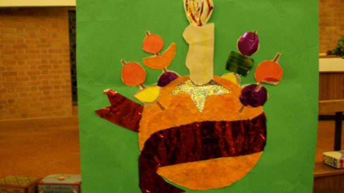 A paper craft christingle on a green background.