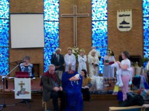 Scratch nativity participants stand in their costumers on the St Peter's stage. One girl wears unicorn outfit.