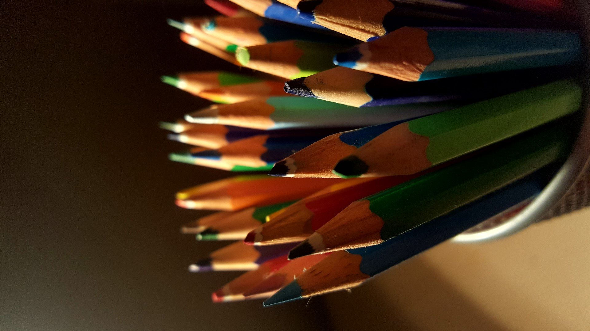 Close up on various colours of pencils in a pot.