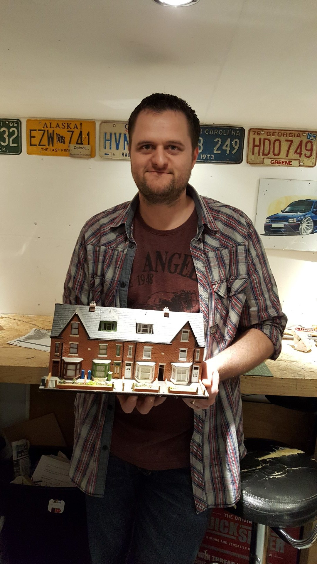 Lee Smithson holds up a miniature he made of his father-in-law's house on Scott Road.
