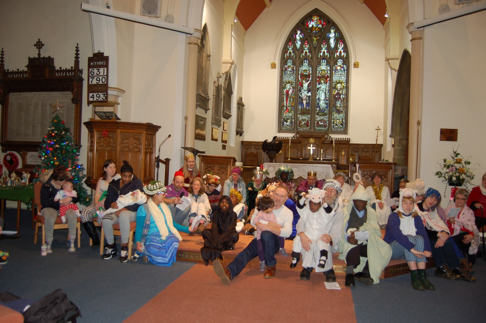 Parents and children sit by the alter in Christ Church dressed in nativity costumes.