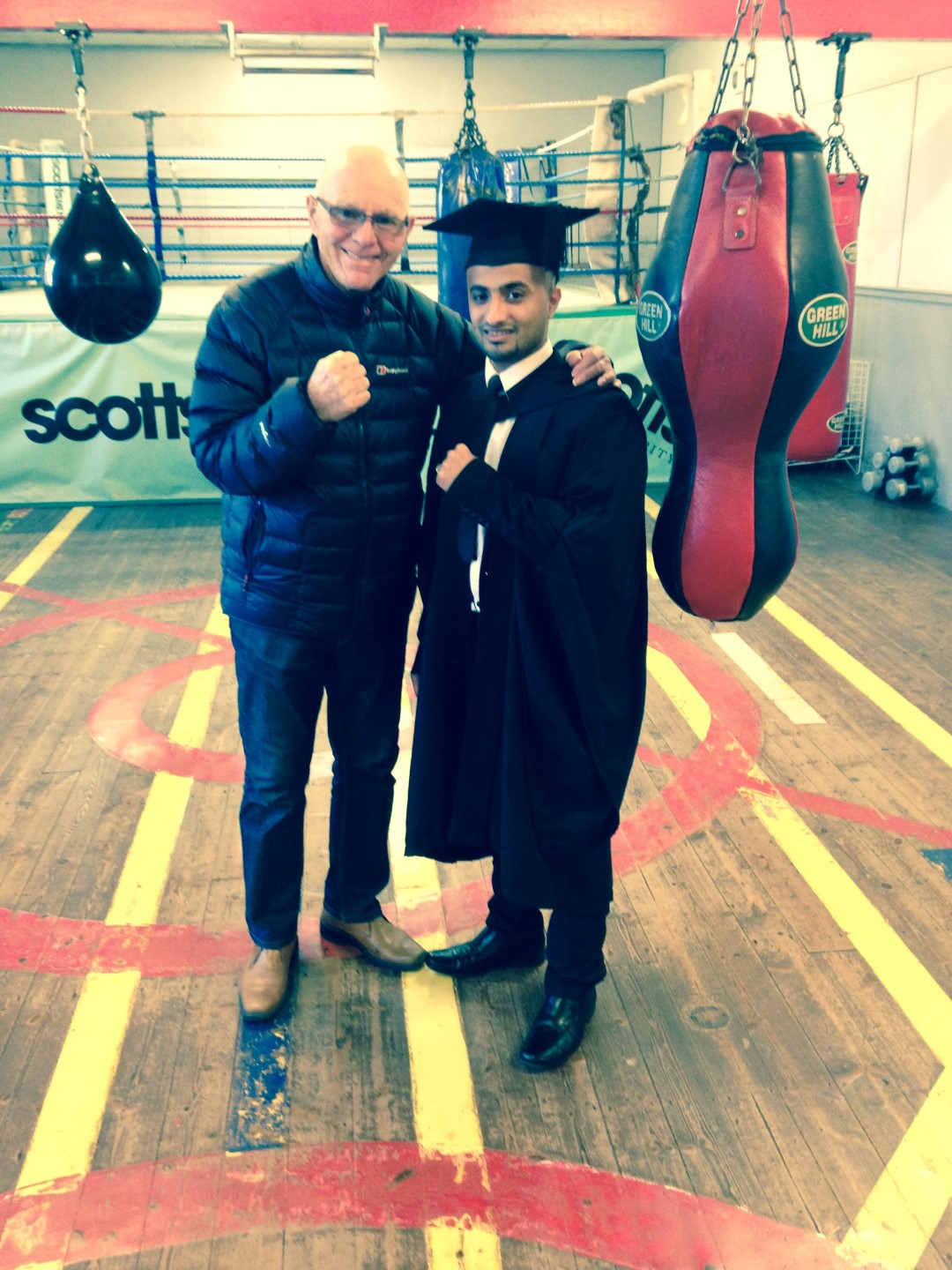 Arsalan, in university gown, and Brendan, stand in front of a boxing ring.