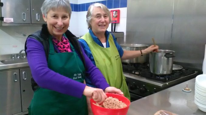 Fir Vale food bank volunteers in the kitchen of St Cuthbert's church, cooking.