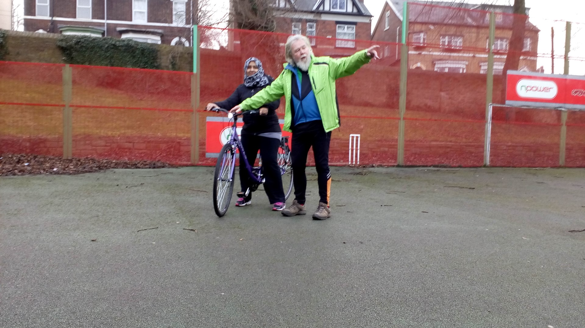 Dave Brennan is pointing while holding the handlebars of a bike ridden by a young learner.