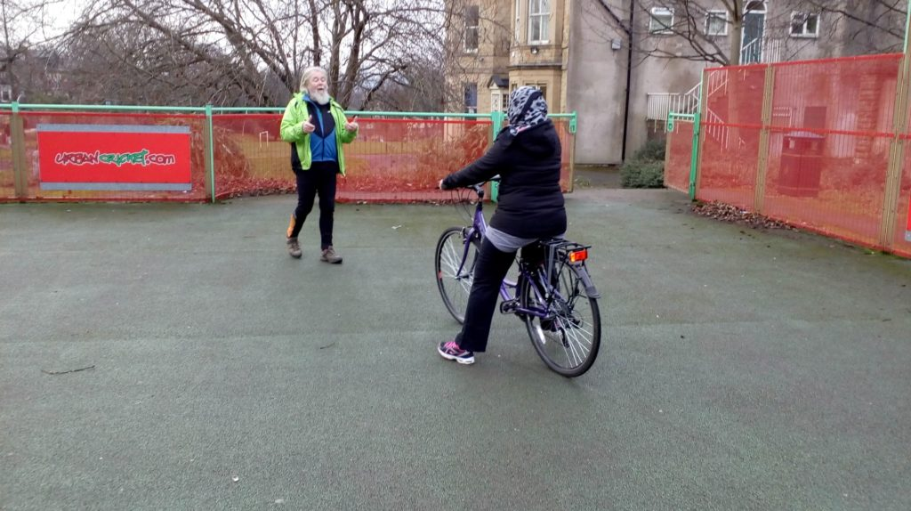 Dave beckoning to a rider who sits on the a purple bike with her feet on the floor.