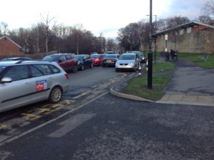 Many cars driving along and parked on Firshill Crescent, nearly the bus stop.