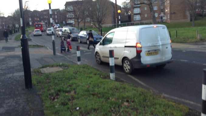 White van waiting in front of zebra crossing on Firs Hill road, where a family is crossing the road.