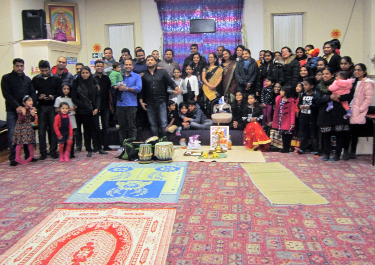 Tens of Hindus stand around colourful mats and instruments at the Hindu Samaj Centre.