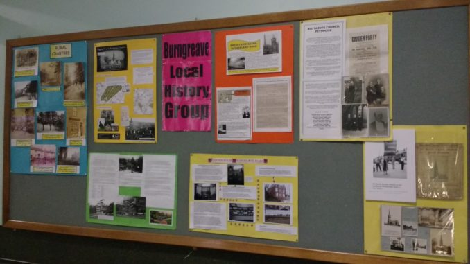 """A board with """"Burngreave Local history Group"""" at the centre has a display of information and pictures, such as a page for All Saints Church, Pitsmoor."""