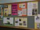 "A board with ""Burngreave Local history Group"" at the centre has a display of information and pictures, such as a page for All Saints Church, Pitsmoor."