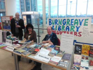 "Three library volunteers sit behind a desk filled with books, Costa coffee cups, and biscuits. The sign reads ""Burngreave Library Volunteers. Can you help us?""."