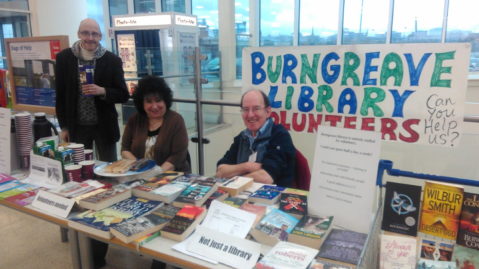 """Three library volunteers sit behind a desk filled with books, Costa coffee cups, and biscuits. The sign reads """"Burngreave Library Volunteers. Can you help us?""""."""