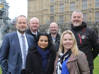 Volunteers and staff from a project Exploring Utopia and Tesco's Community Champions stand in front of Palace of Westminster.