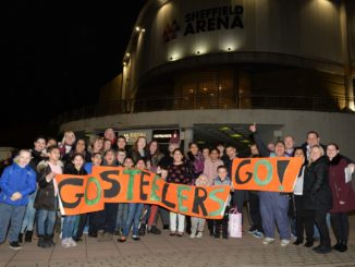 "Children and parents stand outside Sheffield Arena holding a banner reading ""Go Steelers Go!"""