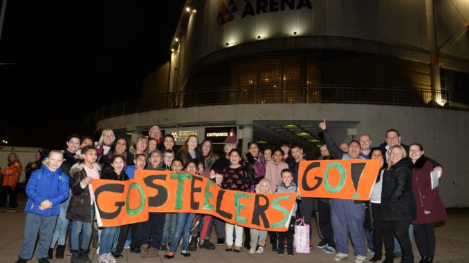"""Children and parents stand outside Sheffield Arena holding a banner reading """"Go Steelers Go!"""""""
