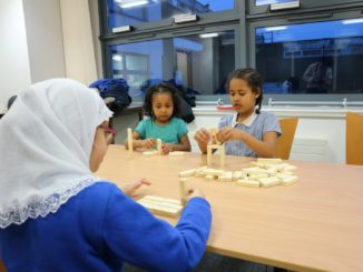Burngreave Library Games club. Little girls build Jenga towers in the library.