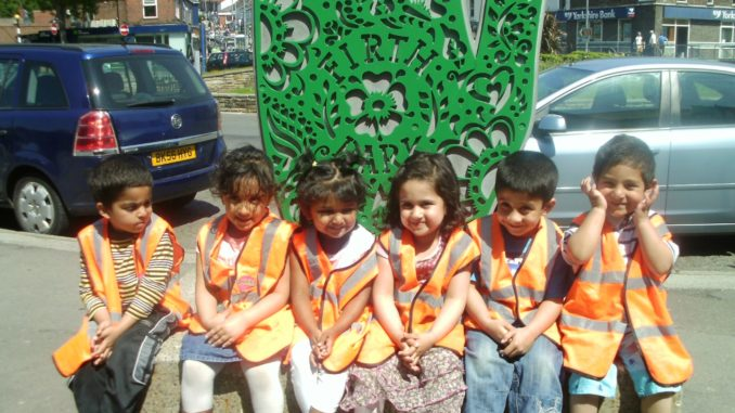 Six children in high vis jackets, sitting in front of a green rangouli hand street sculture with firth park roundabout behind.