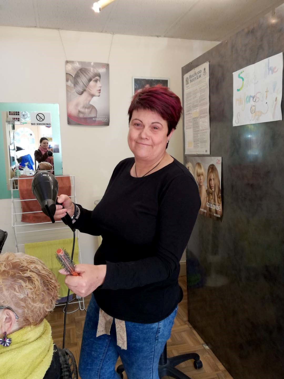A smiling white woman with short red hair and a black top dries the hair or a blonde customer in her salon.